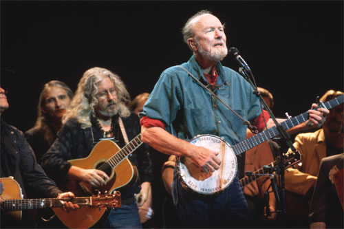 Folk music icon Pete Seeger plays the banjo and sings with Arlo Guthrie (back left) at the Woody Guthrie Tribute Concert at Severance Hall in Cleveland, September 1996.  Credit: Neal Preston/Corbis